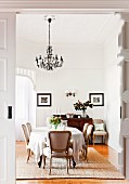 Dining area with antique chairs and large, oval table below chandelier; bay window in background