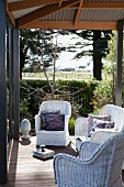 White wicker armchairs on roofed terrace with vintage ambiance; view across sunny garden in rural setting