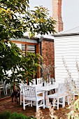 White wooden chairs and table on brick terrace outside house with brick wall, brick chimney and white, wood-clad building to one side