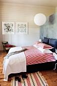 Doppelbett mit rot-weiss gestreifter Bettwäsche vor Raumteiler, im Hintergrund weisse Holzwand in ländlich modernem Schlafzimmer