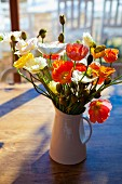 Bouquet of colourful poppies on table in sunshine