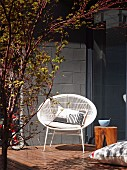 Retro shell chair and stool on wooden terrace with concrete-block wall and dark glass wall in background