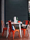 Orange vintage chairs and white table on wooden terrace against grey concrete-block wall of designer house