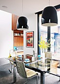 Black, reflective pendant lamps above original 60s, chrome cantilever chairs and glass table in dining area