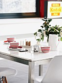 Red and white striped cups on dining table with marble top and metal frames combined with Eames shell chairs