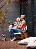 Mother and child sitting in shell chair on terrace against concrete block wall