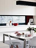 Rot-weiss gestreifte Tassen auf Esstisch mit Marmorplatte und Metallgestell, dazu klassische Schalenstühle von Eames; im Hintergrund Einbauküche