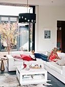 Bright living room with folding sliding doors to courtyard; young woman relaxing on corner sofa with scatter cushions