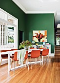 Red-brown shell chairs around table in corner next to window in front of green-painted wall in open-plan dining area