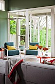 Sofa opposite blue easy chairs with yellow scatter cushions next to open terrace doors with view into garden
