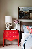 White table lamp on red vintage bureau next to bed below framed picture