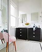 Twin washstands with black base units below mirrors and pink fifties armchair on pale tiles floor