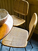 Fifties chairs with metal frames and cane seats and backrests at round, polished wooden table