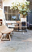 Hand-crafted wooden bench on concrete floor in front of seating area and tall houseplant against glass wall