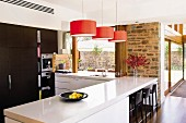 White counter-style table below red pendant lamps in contemporary kitchen area