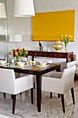 Ecru upholstered chairs around set dining table in front of antique sideboard below monochrome yellow artwork on wall