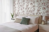 Elegant, bright bedroom with bird-patterned wallpaper and scatter cushions on double bed with upholstered headboard