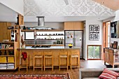Wooden cupboards, counter and bar stools in open-plan kitchen in traditional interior