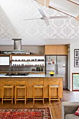 Modern kitchen area with wooden counter and bar stools in open-plan interior