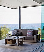 Coffee table and matching sofa with brown cushions and patterned scatter cushions against glass balustrade in relaxation area on roofed wooden deck with view of Pacific Ocean