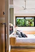 View through open door of stacked pillows on floating modern bed and palm trees seen through open window