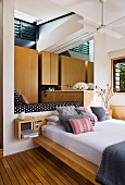 Stacked pillows on modern bed below daybed in niche in contemporary house