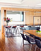 Dining table, dark wicker chairs and designer bar stools at kitchen counter in front of wooden, flat-fronted fitted kitchen cabinets
