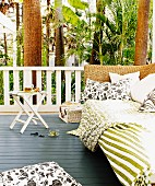 Cushions and blankets on wicker daybed in relaxation area on veranda in tropical surroundings