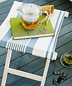 Glass teapot and book on stool with white and blue striped seat on grey wooden floor