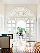 View of terrace through large, arched window element behind elegant 20s-style armchair and marquetry parquet floor