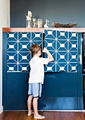 Boy opening door of blue-painted cabinet with graphic pattern