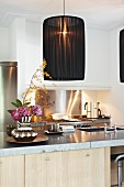Pendant lamp with black, fabric lampshade above counter with sink and vase of flowers; illuminated gas stove in background