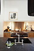 Undermount sink with vintage tap fittings in dark worksurface and illuminated gas stove in background