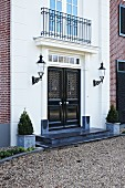 Entrance of prestigious villa with double doors flanked by sconce lanterns