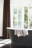 Free-standing, anthracite bathtub with vintage tap fittings and sunshine falling though half-open, glass French doors