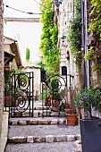 Wrought iron gate with curved elements in front of terraced pathway and Mediterranean, stone houses