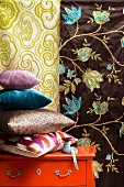 Stack of scatter cushions on orange chest of drawers in front of two lengths of floral fabric