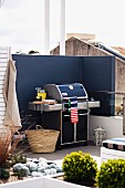 Barbecue against screen wall painted dark blue on modern roof terrace