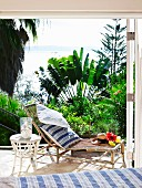 Bamboo sun lounger and white wicker table on sunny terrace with sea view and tropical plants