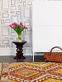 Vase of tulips and designer stool against wall with pattern of rectangles; kilim rug with traditional pattern in foreground