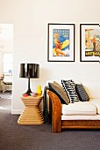 Framed retro posters above wicker sofa next to black table lamp on designer stool