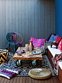 Upholstered bench with colourful scatter cushions and rustic side table on castors against blue, wood cladding