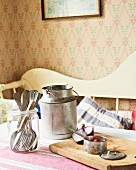 Milk churn, cutlery, onions and saucepan on kitchen table