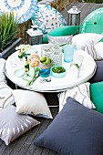 Food and drinks on round, low table surrounded by various floor cushions on wooden deck
