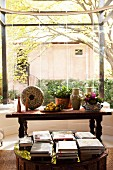 Stacks of books on low table in front of flowers and vases on antique wooden table in semi-circular bay window with view of courtyard