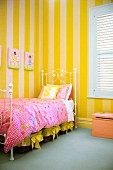 Pretty bedroom for a girl - delicate metal bed frame and floral bed linen against wall with yellow striped wallpaper