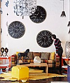 Yellow stool and wooden coffee table on animal-skin rug in front of sofa below collection of vintage clocks on wall