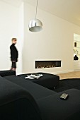 White living room with black sofa set and fireplace integrated into wall