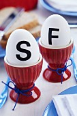 Eggs with stick-on initials in red eggcups on breakfast table