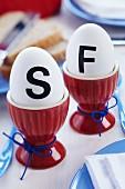 Eier mit schwarzen Initialen beklebt in roten Eierbechern auf Frühstückstisch